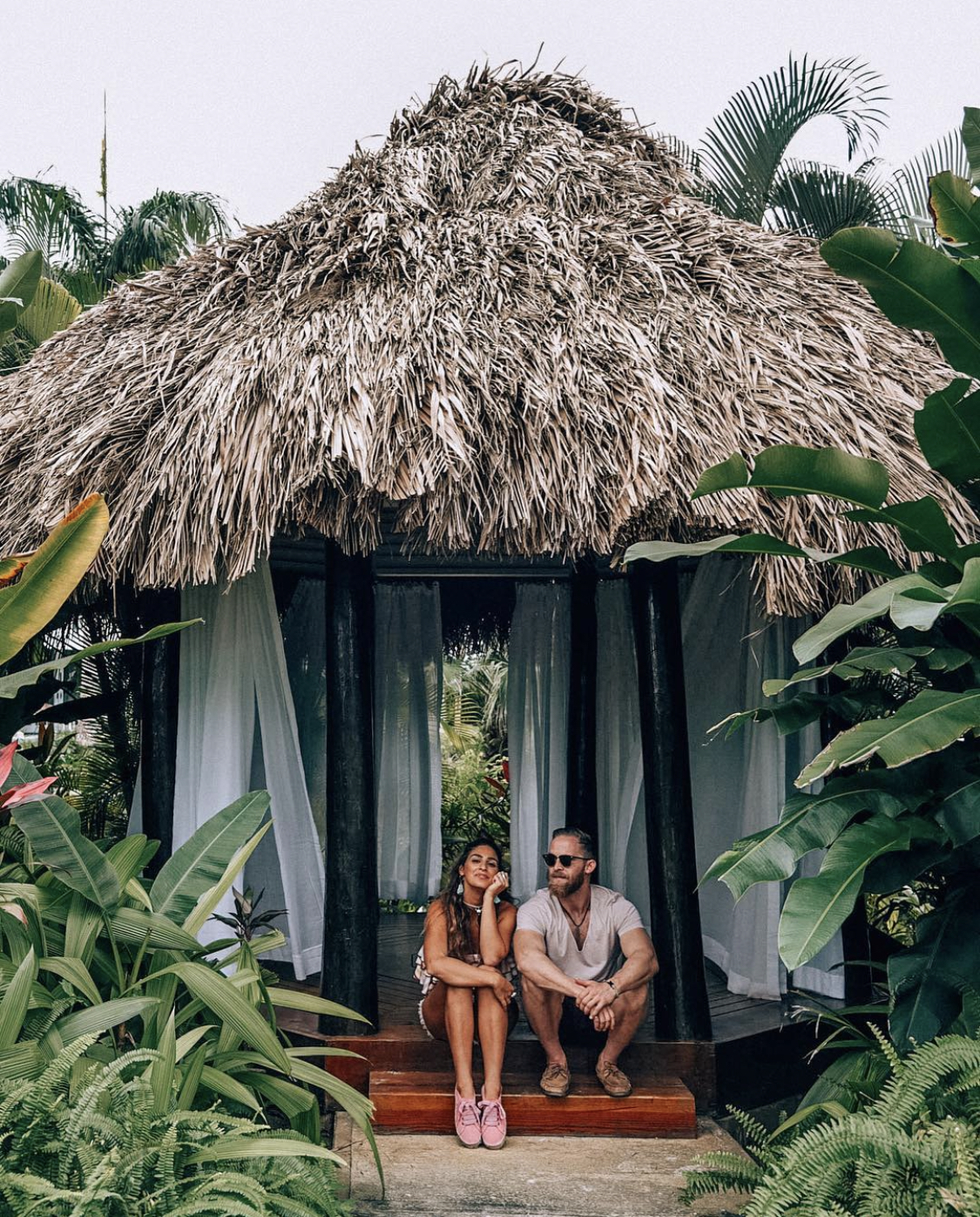Couple sitting in front of a beach hut in Jamaica
