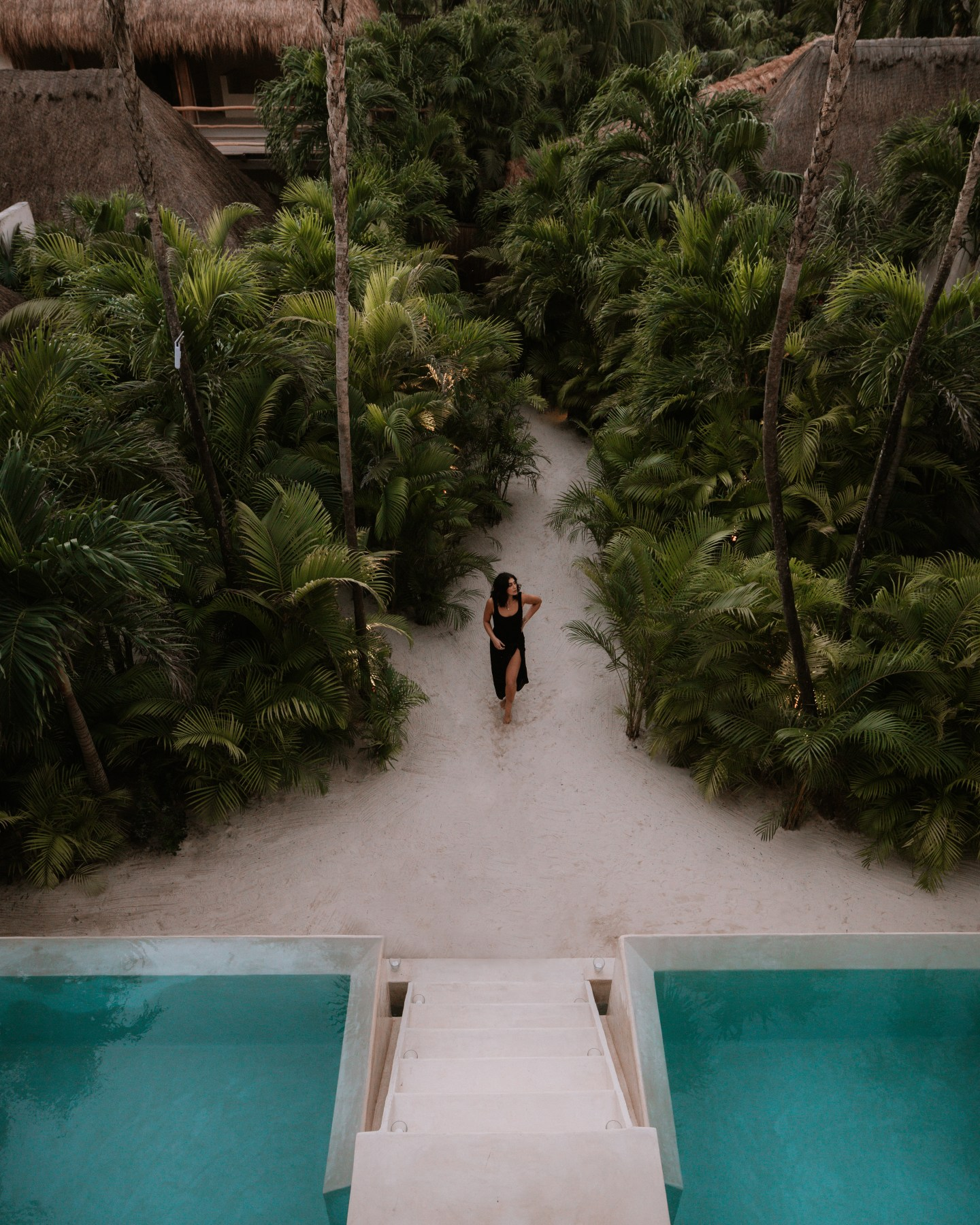 Girl walking in the palm tree path that leads to the pool at La Valise in Tulum Mexico