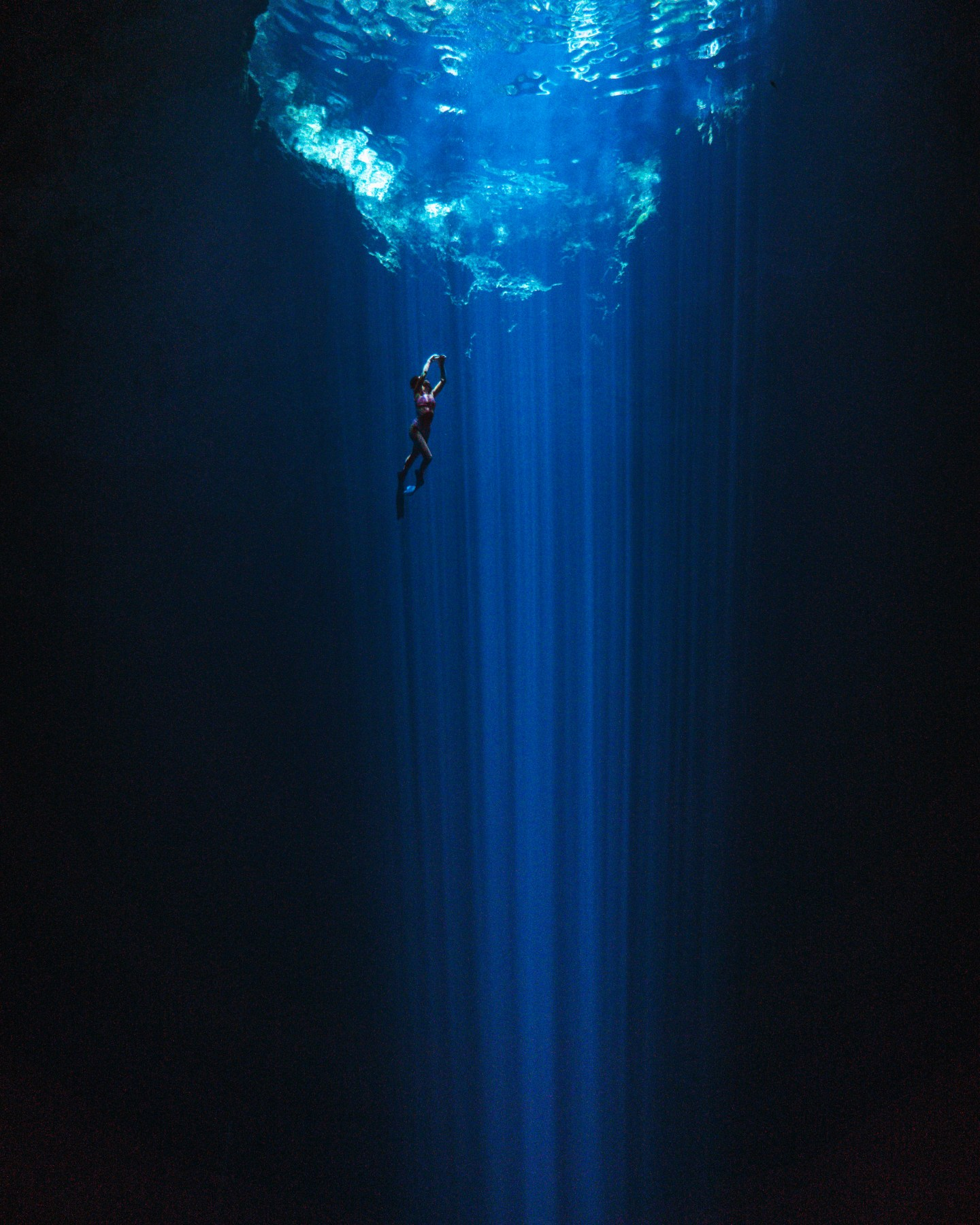 woman freediving in a cenote in mexico